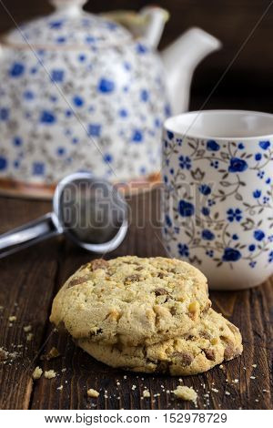 Morning tea with biscuits on natural wooden table.