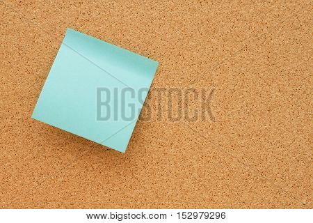 Bulletin board with a blank teal sticky note with copy space for your message