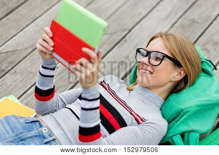 Cheerful girl with the tablet in their hands lies on Backpack on wooden surface