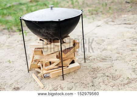 Cooking on a fire. Ignition of a fire. Food in a cauldron on a fire. Food outdoors. Cooking outdoors. Cooking in nature on the cauldron.
