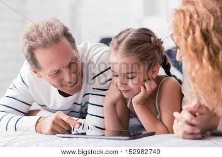 Look at this. Happy little girl lying on the bed with her grandparents while looking at the tablet and having fun at home
