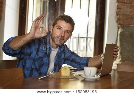 young attractive businessman or student on his 30s wearing casual clothes working or studying with laptop computer at coffee shop drinking tea cup and cake in modern business self employed concept