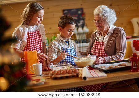 grandmother enjoying with children making Christmas cookiesat home