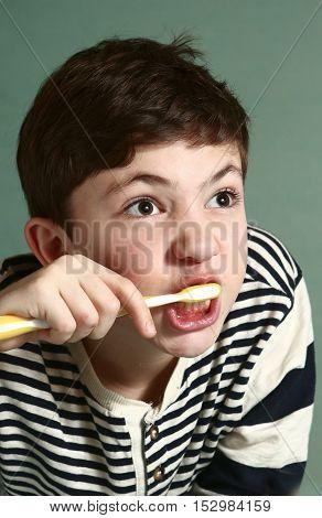 teen boy brushing his teath neat boy
