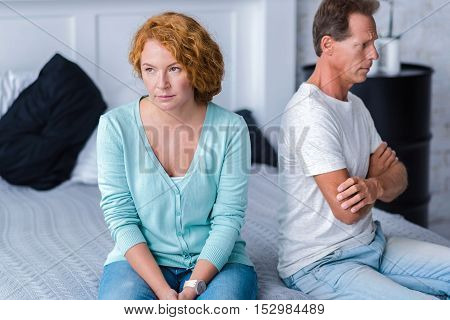Quarrelsome. Irritated husband and wife sitting back to back on the bed with crossed arms