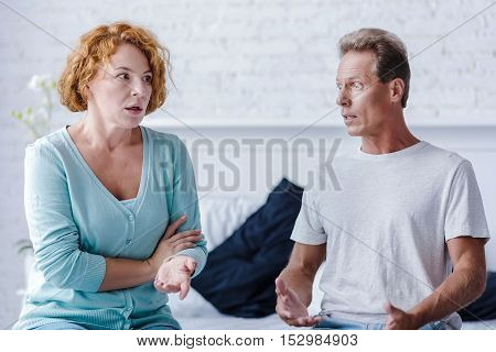 Dont you hear me. Shocked senior couple sitting on the bed while arguing at home