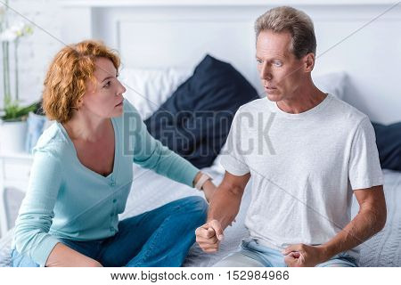 I hitting you now. Furious husband going to hit his wife while sitting on the bed and arguing