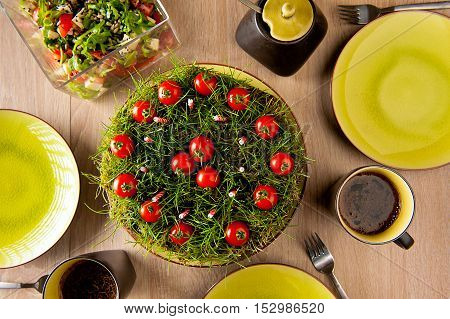 An improvised garden cake made from ground grass candles and cherry tomatoes.