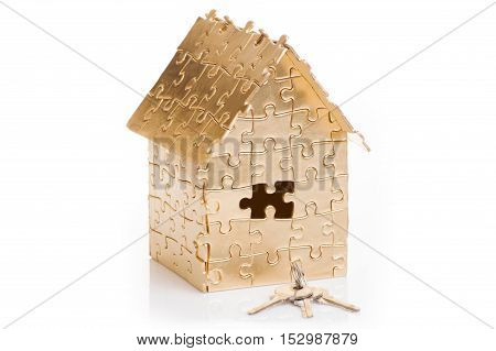 home of gold color puzzles with a keys isolated on white background. Concept: time to buy a house