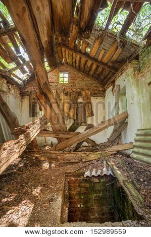 Chernobyl Disaster. The Interior Of Ruined Abandoned Private Country House With Caved Roof In Exclusion Area After Terrible Consequences Of The Nuclear Contamination.