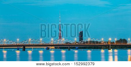 Riga, Latvia. Two Bridges Over Daugava Together: Stone Akmens And Railway Bridge In Evening Illumination With Red Radio TV Tower Background In Summer Dusk Under Blue Sky. poster