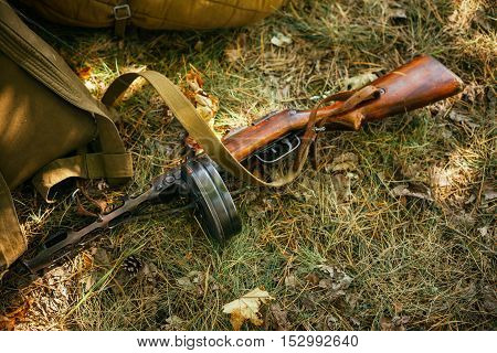 Soviet russian military ammunition - submachine gun of World War II on ground. Focus is pointed at ladybug sitting on the cage of the submachine gun.