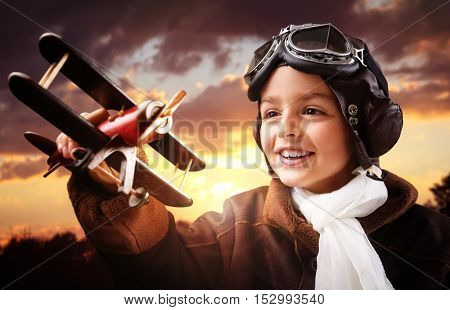 Boy wearing old-fashioned aviator hat, scarf and goggles holding a wooden biplane up in the air with sunset