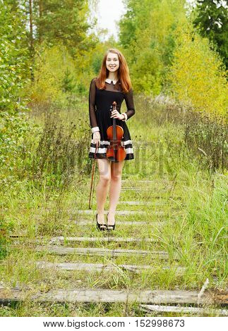 Smiling beauty girl with violinon on the old railroad in the forest