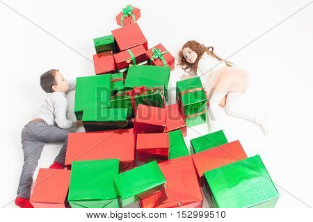 Merry Christmas 2016. Black Friday 2016. Cute little kids climbing by many Cristmas gifts at white background. Children happy to receive many gift boxes. Shopping sale at Xmas