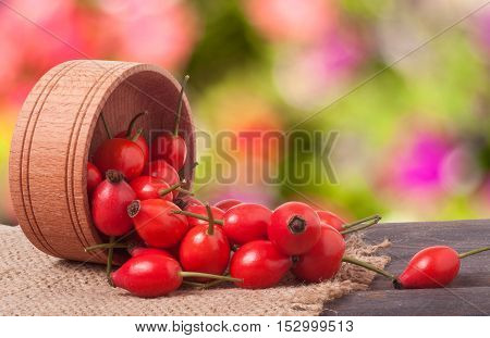 rosehips in wooden bowl on a dark board with sackcloth with a blurred background.