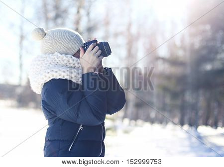 Child little boy photographer takes picture on the digital camera outdoors in winter sunny day over blurred forest background view profile