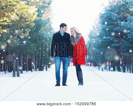 Christmas, Winter And People Concept - Happy Young Smiling Couple Walking Together Having Fun In Win