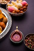 Mix Mithai and diya on diwali over colourful background poster