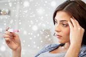 pregnancy, fertility, maternity, winter and people concept - sad unhappy woman looking at pregnancy test at home over snow poster