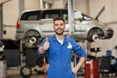 car service, repair, maintenance, gesture and people concept - happy smiling auto mechanic man or smith showing thumbs up at workshop poster