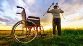 Miracle recovery: Old man gets up from wheelchair and raises hands up. Shot in a meadow. Recovery concept poster