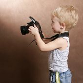 child in studio with professional camera poster