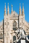 Facade of the Duomo di Milano (Milan Cathedral 1418-1577) and lion statue. Church monument symbol of Lombardy and of Italy poster