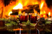 Christmas New Year composition. Two glasses of mulled red wine or hot drink tea with christmas decoration - fir branches in front of warm fireplace. Romantic, relaxed magical atmosphere near fireplace poster