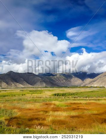 Beautiful View Of Colorful Natural Meadow Grass Field With Asian Mountain Ranges And Blue Sky Backgr