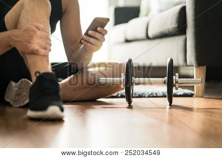 Man Using Smartphone During Workout At Home. Online Personal Trainer Or On Mobile Phone. Internet Fi