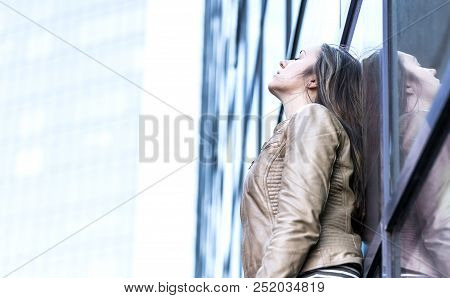 Stressed, upset, depressed and emotional woman. Sad person leaning against building. Anxious lady alone in city. Burnout and pressure from work concept. poster