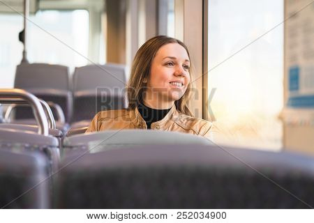Happy Lady Looking Out The Window In Bus, Train, Tram Or Subway. Smiling Woman Riding Public Transpo