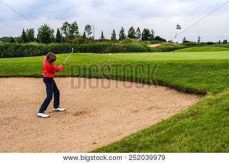 12 Years Old Boy Playing Golf At Golf Course