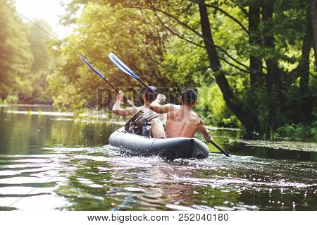 Rafting On The River In A Kayak In The Summer Season. Leisure. Two People In The Boat Row With Oars.
