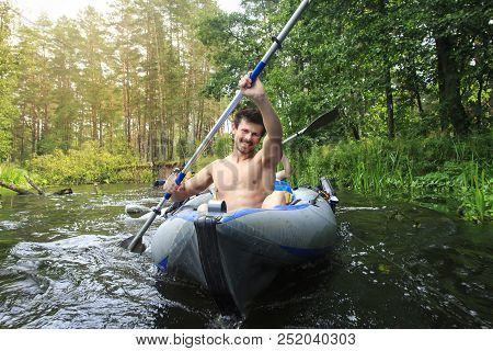 Rafting In A Canoe By The River. Young Guys With Oars In A Boat Sail On The River In The Summer. Act