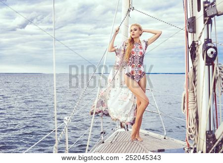 Beautiful fashion model posing on a sailing boat in swimsuit.