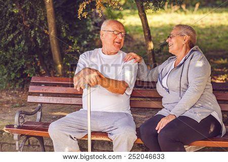 Smiling Pensioner Couple Sitting Together On A Park Bench