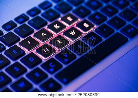 Fake News Written In Red On A Backlit Laptop Keyboard Close-up With Selective Focus In A Blue Ambian