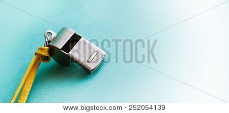 Vintage Silver Whistle On Green Paper Background. Referee Trainer Sport Competition Sound Instrument
