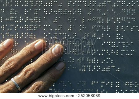 The Fingers Are Touching The Metal Plate Written In The Braille Letters; Helps The Blind To Recogniz