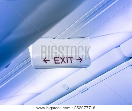 Vintage tone emergency exit sign with red arrow on ceiling of airplane. Illuminated evacuation symbol underneath the overhead compartments. Shining signboard show escape of emergency, urgency concept poster