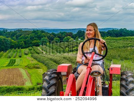 Beautiful Woman On A Red Agricultural Tractor, Green Field, Landscape Of Meadow With Grass Upstate N