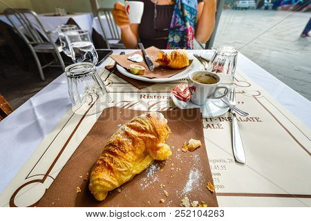 Florence, Italy - September 21 2017: A Half Eaten Croissant And Breakfast At A Sidewalk Cafe As A Co