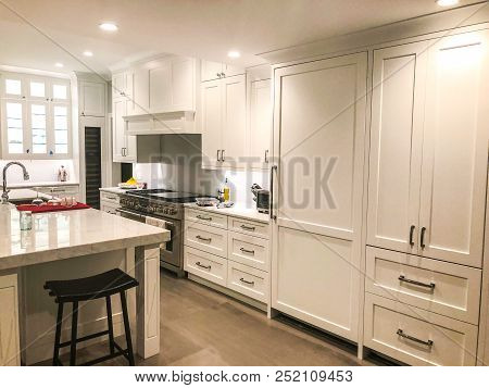 white kitchen with island countertop, under mount sink and stainless still appliances, very expensive kitchen cabinets, kitchen interior design, shaker wood kitchen cabinet design