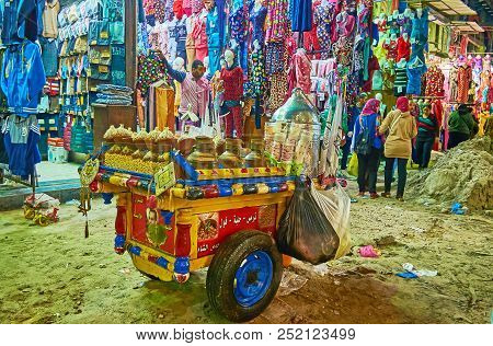 Alexandria, Egypt - December 18, 2017: The Old Wooden Cart With Snacks And Drinks Among The Garment