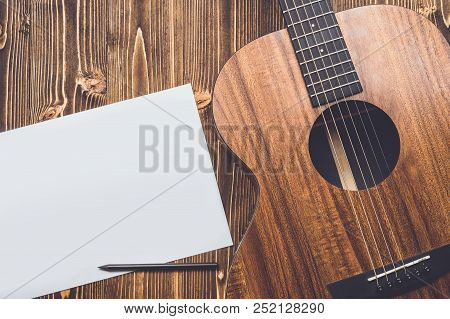 New Brown Guitar On Wooden Board