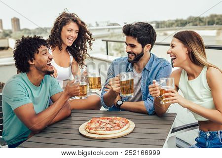 Friends Enjoying Pizza. Group Of Young Cheerful People Eating Pizza And Drinking Beer While Sitting