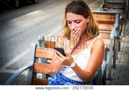 A Beautiful Blonde Caucasian Girl Gets Bad News On A Phone, Shocked By The News And Closing Her Mout