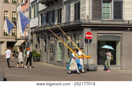 Zurich, Switzerland - August 1, 2018: People Carrying Alpine Horns Passing Along A Street In The Old